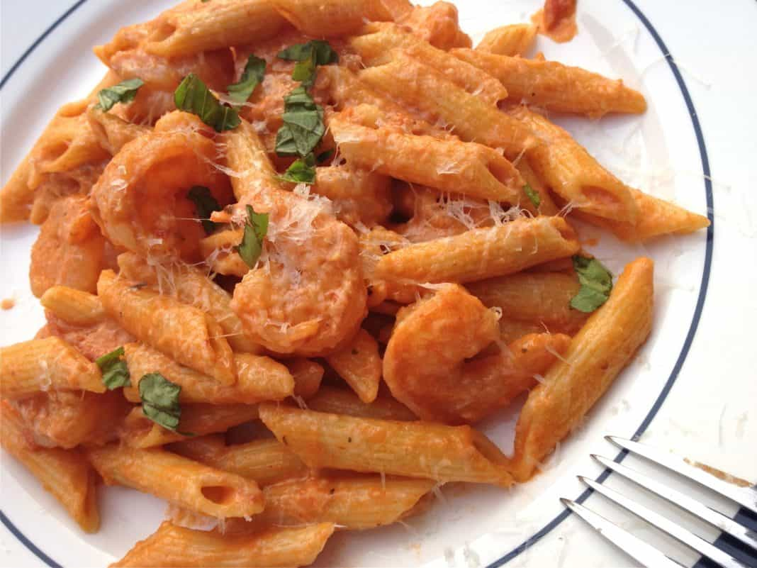 A closeup of a plate of Shrimp and Penne Pasta with Creamy Marinara Sauce topped with grated parmesan cheese and a fork is resting on the side of the plate
