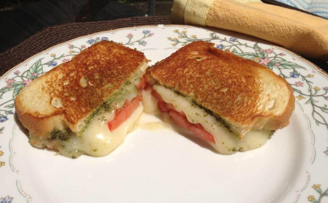 Grilled Fresh Mozzarella, Tomato and Pesto Sandwich cut in half on a plate