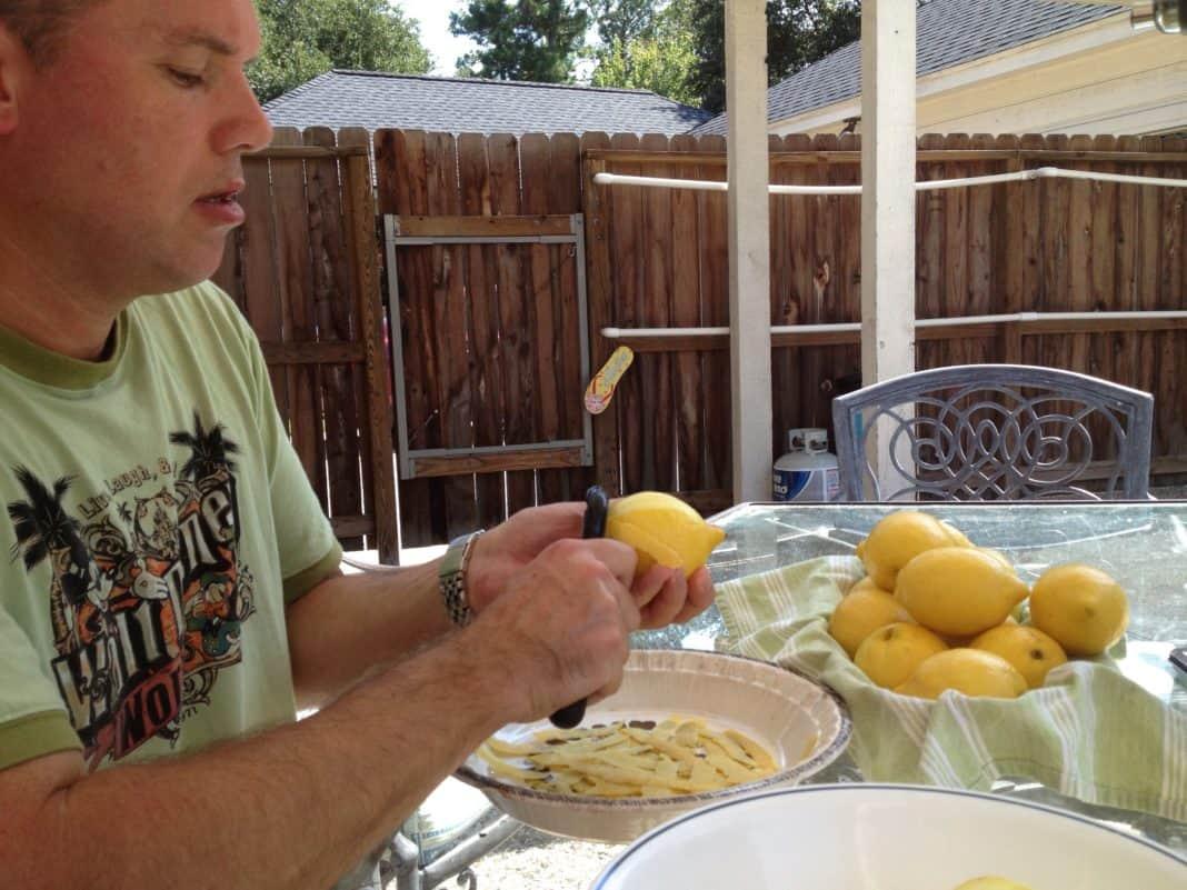 A man peeling lemons in preparation for making limoncello