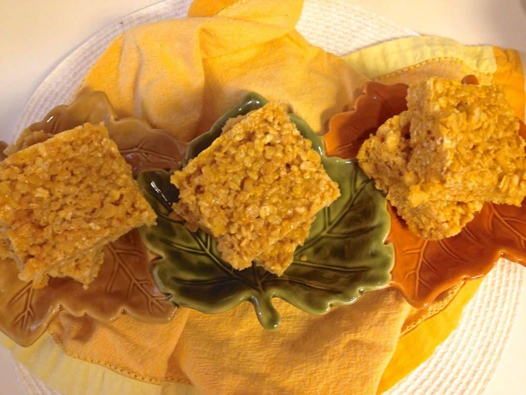 An overhead view of Six Pumpkin Spice Rice Krispies Treats in a leaf-shaped serving bowl