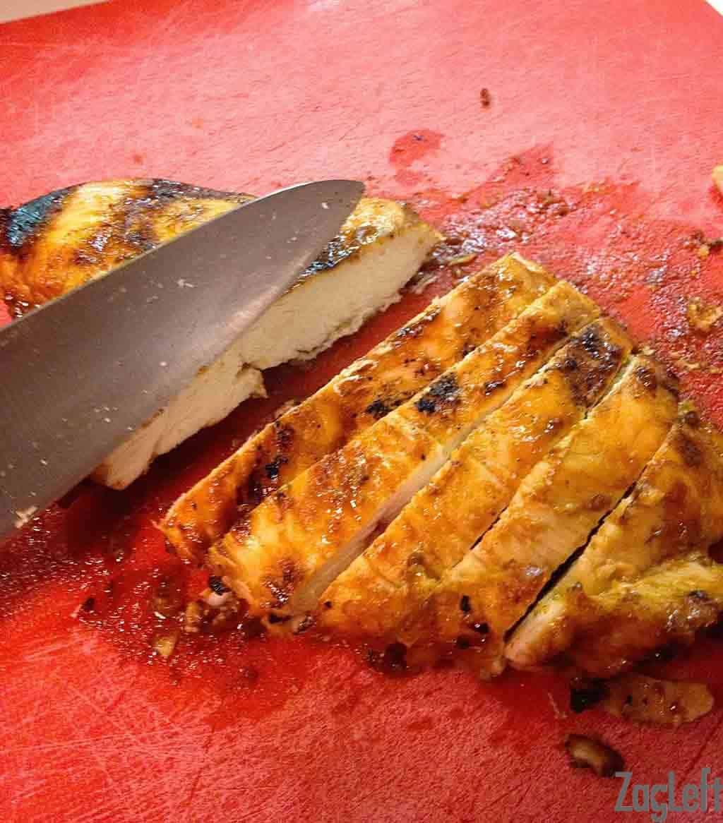 Honey Sriracha Glazed Chicken being sliced into strips on a cutting board