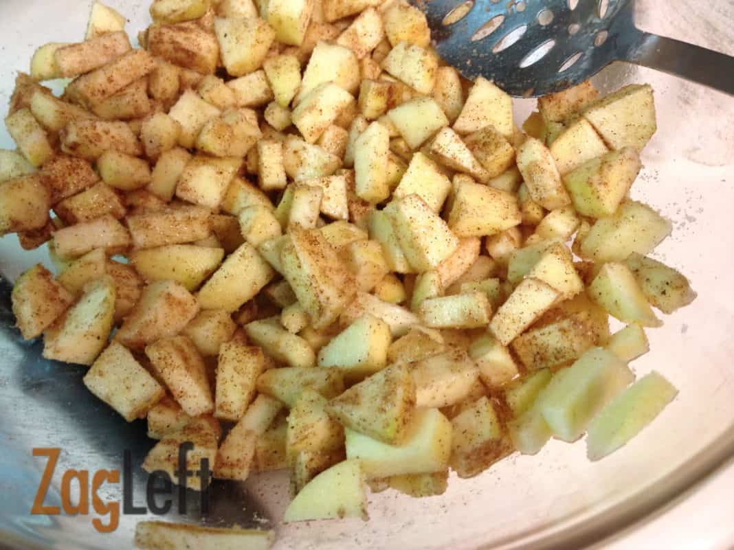 Chopped apples coated in cinnamon sugar in a large mixing bowl with a spoon