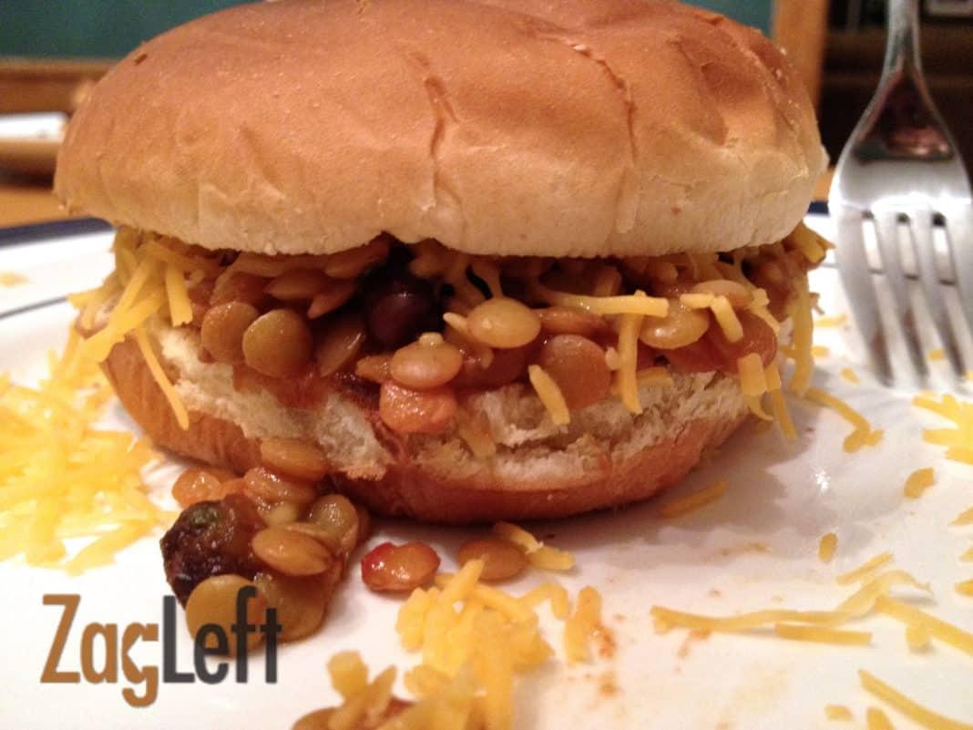 Vegetarian Sloppy Joe with shredded cheese on a whole wheat hamburger bun on a plate