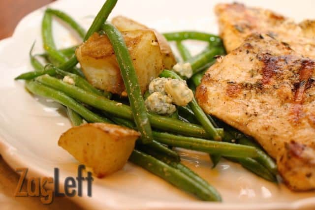 Closeup of a plate of Roasted Potatoes and Green Beans with Bleu Cheese Crumbles and grilled chicken