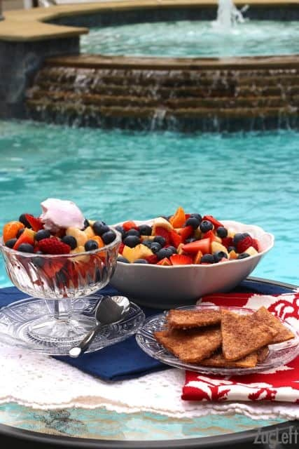 Sliced strawberries, apples, bananas, and oranges topped with whipped cream in a dessert glass next to a bowl of fruit and a small plate of cinnamon sugar crisps with a pool in the background
