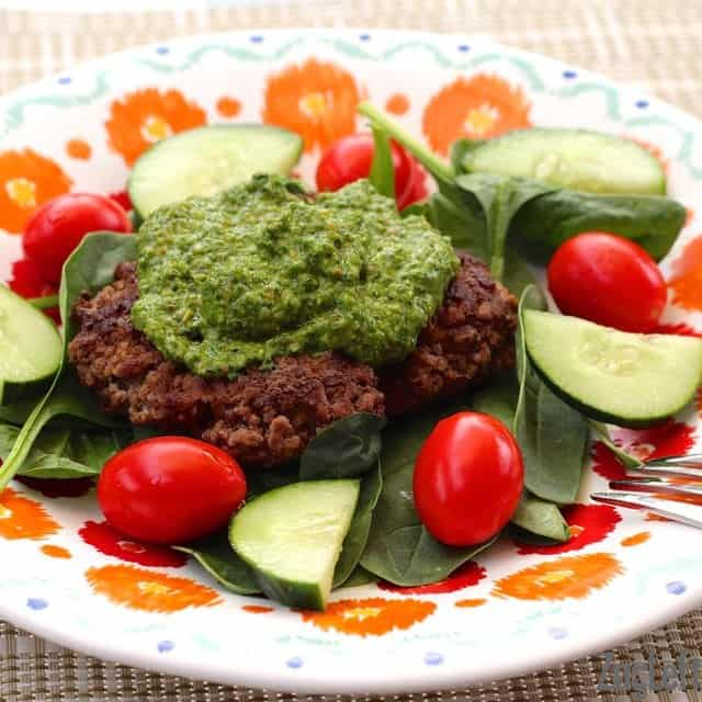 Spinach Pesto on top of a burger on a bed of spinach leaves, sliced cucumbers, and cherry tomatoes on a plate