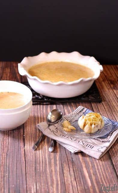 A large serving bowl of Roasted Garlic and Brie Soup next to a small bowl of soup, a small plate of roasted garlic and two spoons