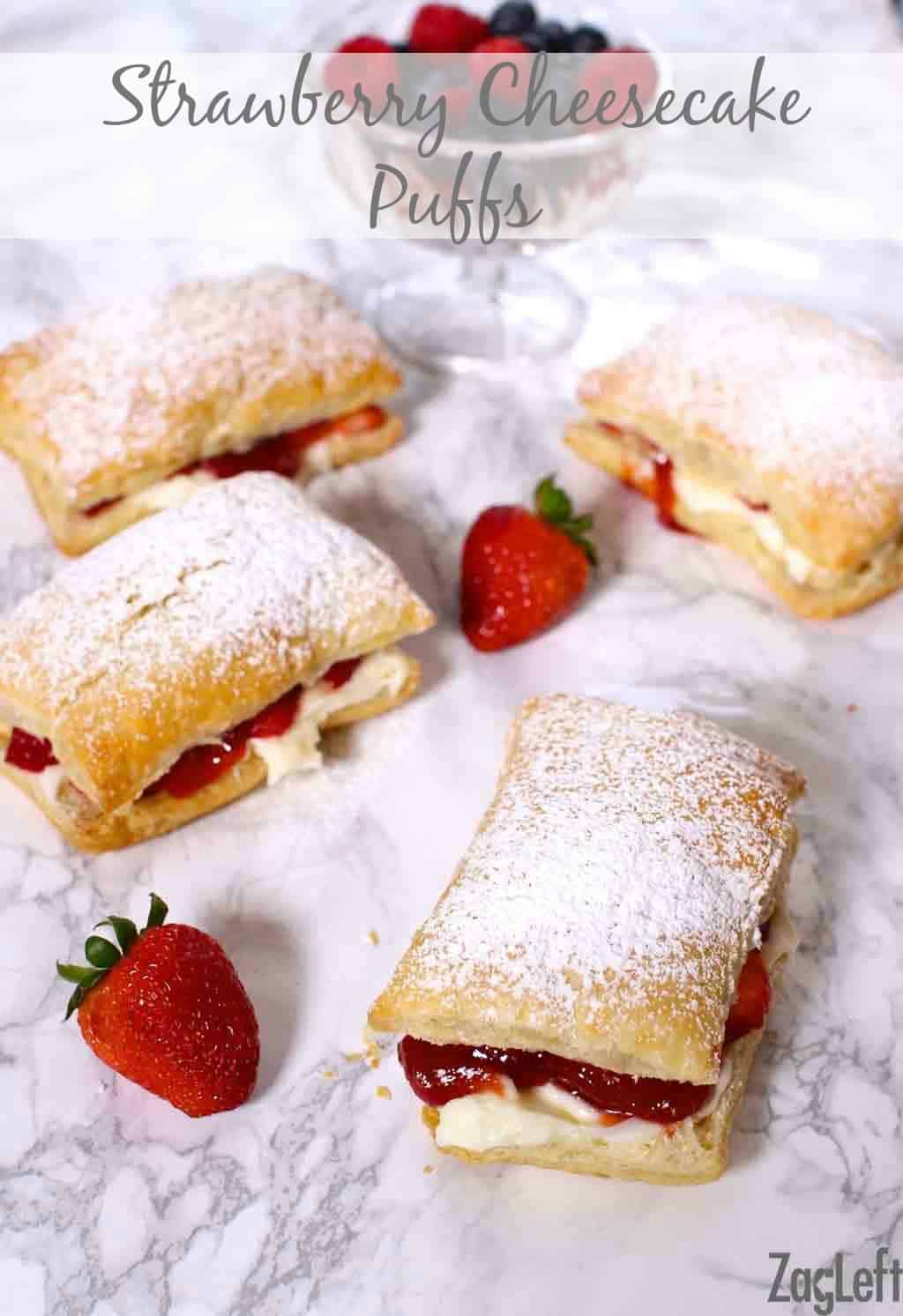 Four Strawberry Cheesecake Puffs dusted with powdered sugar next to a bowl of strawberries