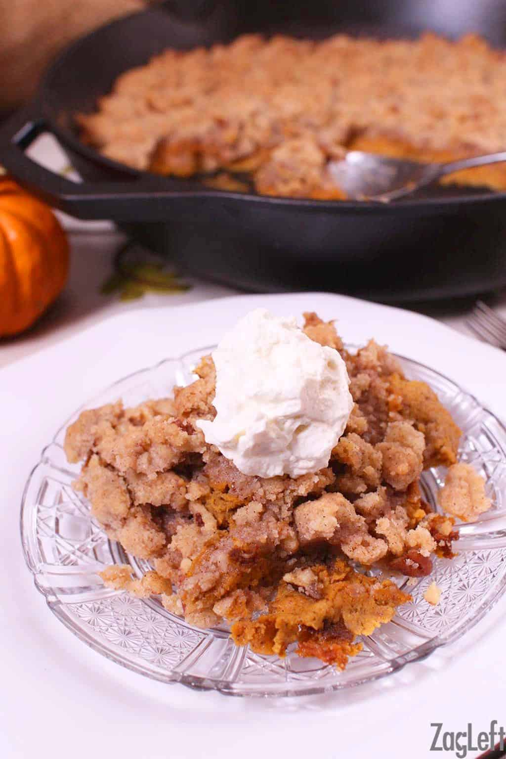 A slice of Crustless Pumpkin Pie with streusel topping and whipped cream on a small plate next to a cast iron skillet with the remainder of the pie