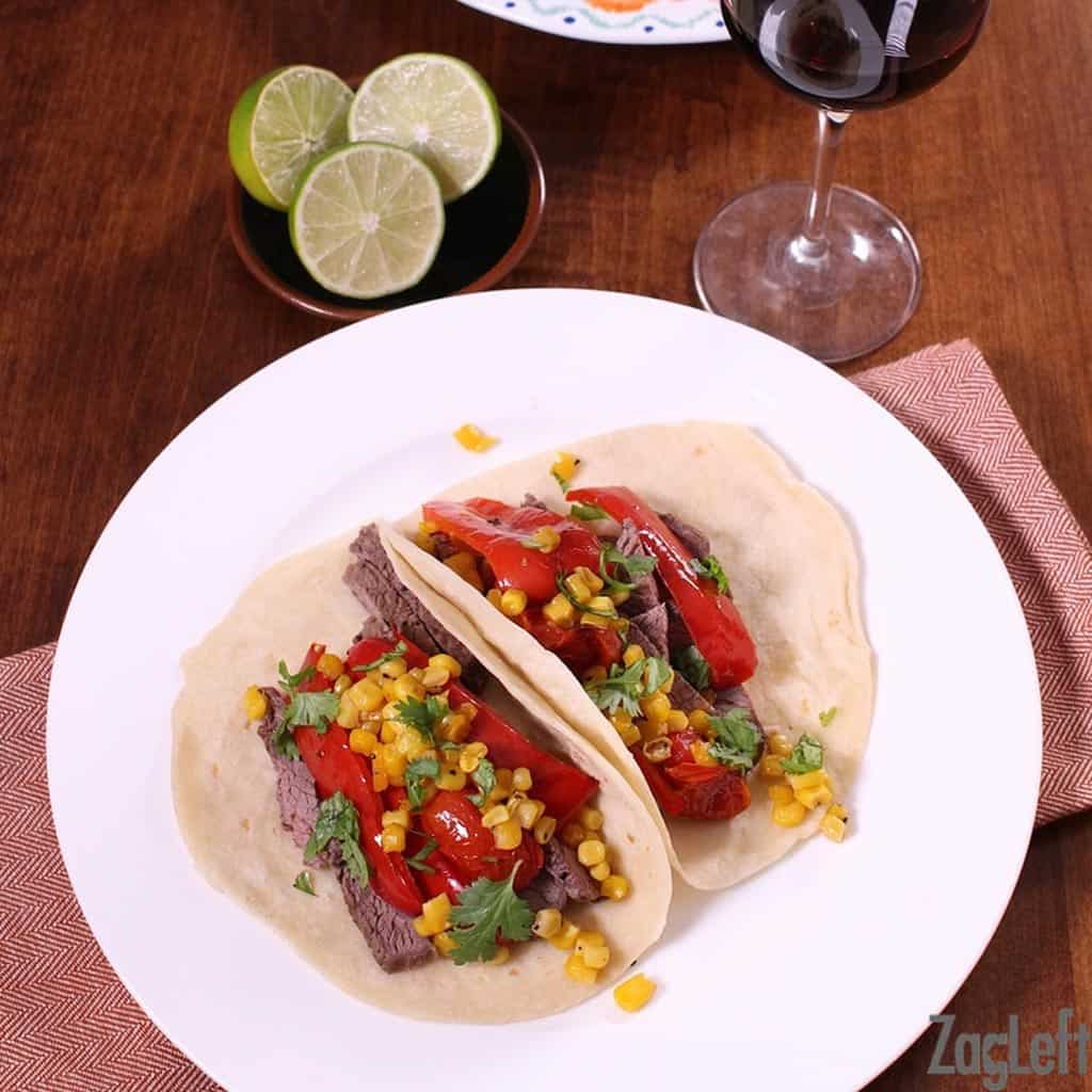 Overhead view of two tacos with strips of steak, strips of red bell pepper, corn, and cherry tomatoes on a flour tortilla topped with cilantro next to a small plate of lime halves and a glass of red wine