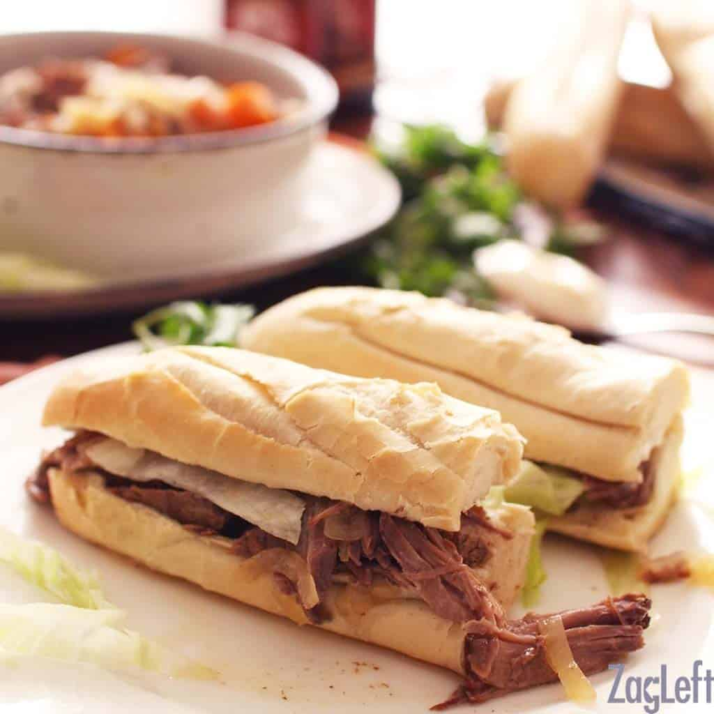 Two halves of a Roast Beef Po-boy on a large plate