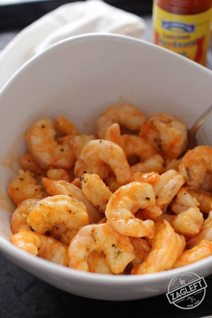 Grilled shrimp coated with buffalo sauce in a bowl